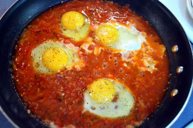 Make a little hole in the salsa, and break in the eggs one at a time ...